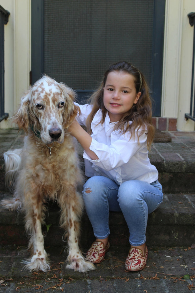 caroline with pet dog in sumak kilim loafers, part of childrens shoes collection.