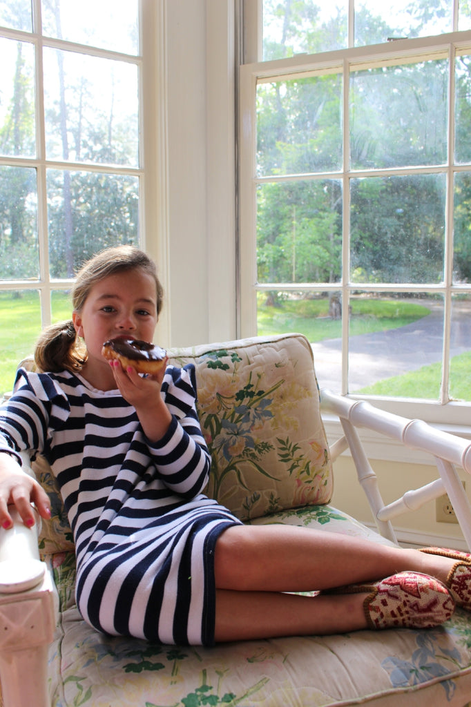 caroline eating donut in indoor patio in sumak kilim loafers, part of childrens shoes collection.