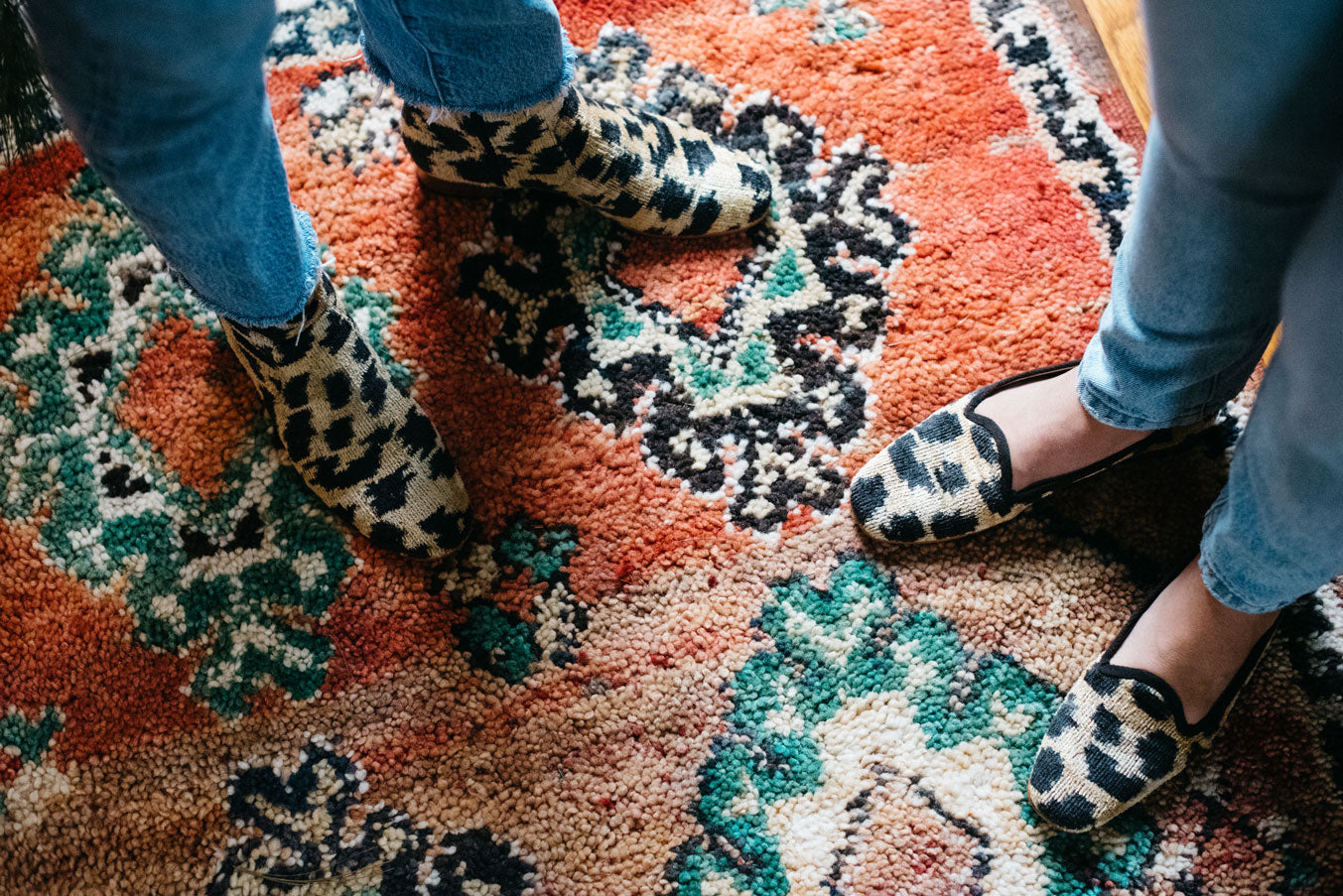 Our leopard print loafers worn on a moroccan carpet next to our matching velvet boots.