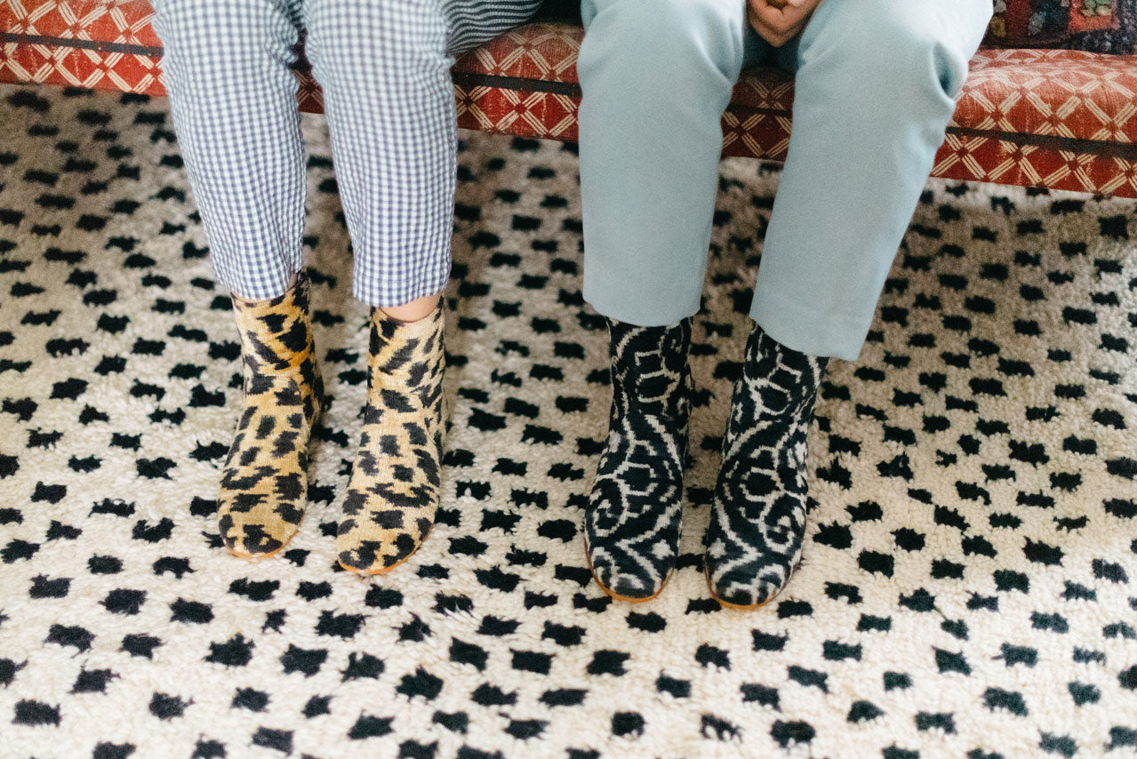 Our leopard print and black and white velvet boots on a moroccan carpet, worn by our designer and her sister in her home.