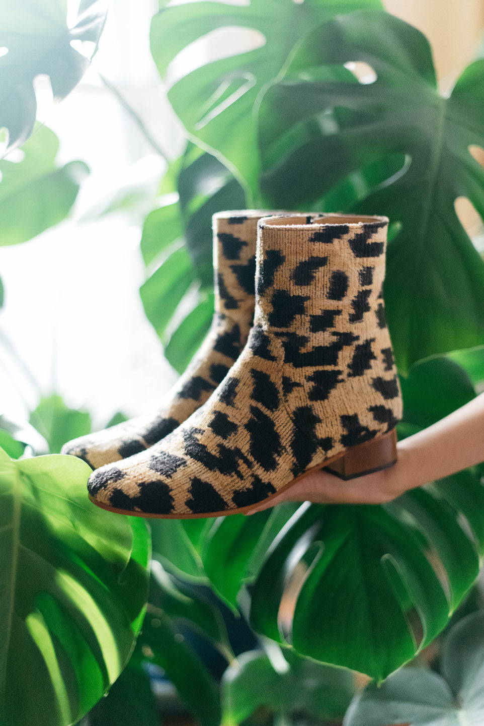 Our velvet leopard print boot photographed in front of a large plant in the designer's home.