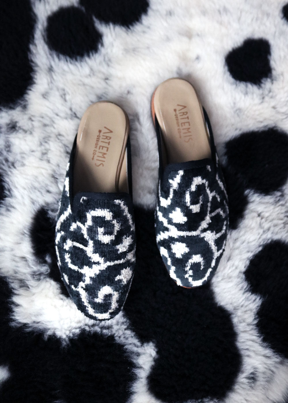 Our black and white velvet slippers on a cow hide.