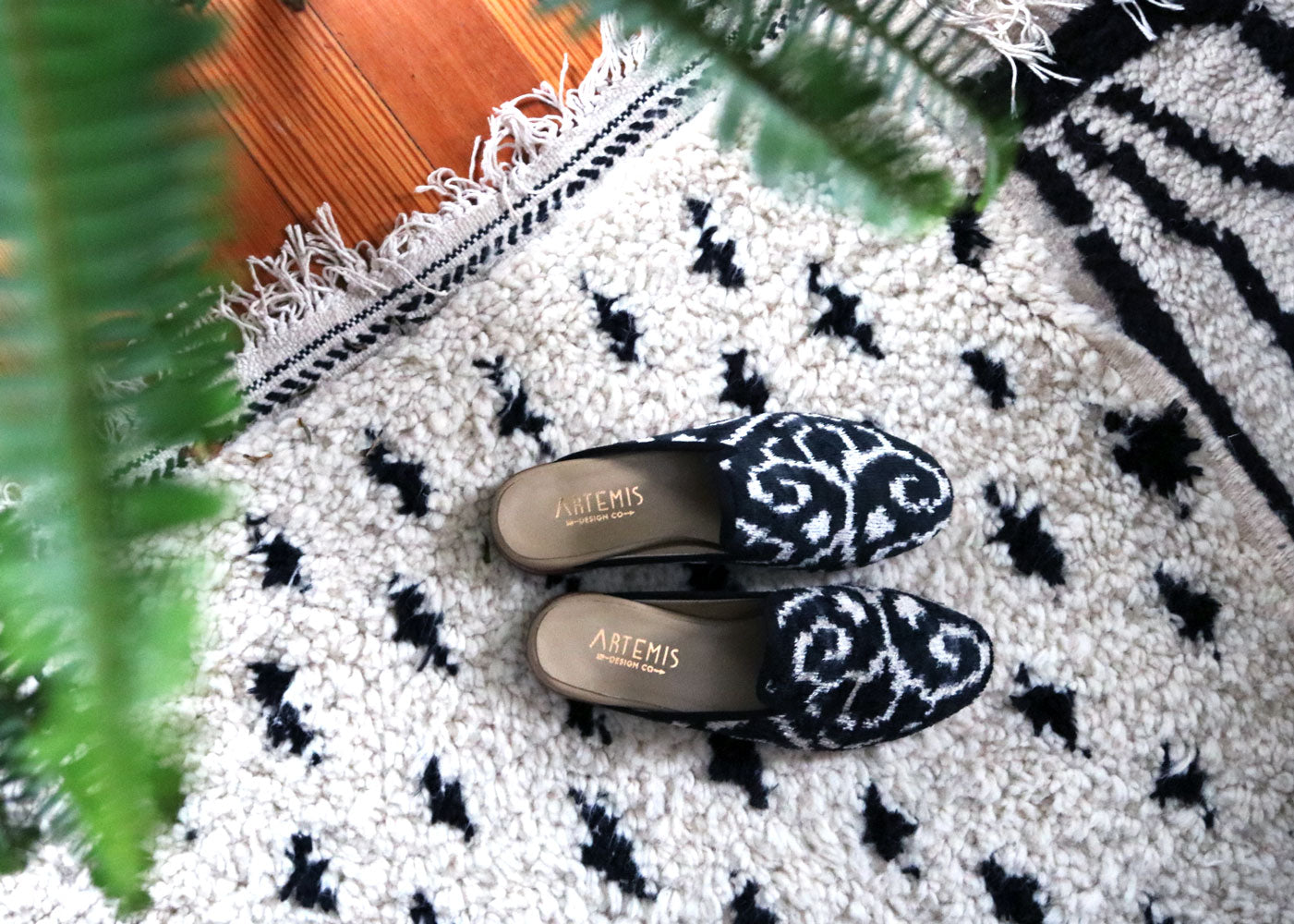 our black and white velvet slippers on a moroccan carpet in milicent's home.