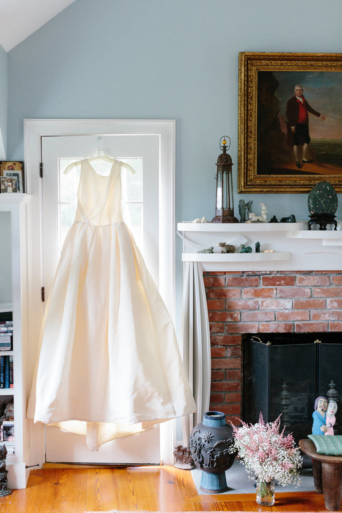 Milicent's wedding dress hanging up while she is getting ready.