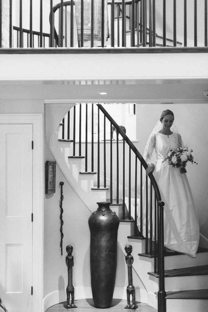 bride in her dress and pearl velvet slippers entering down the stairs