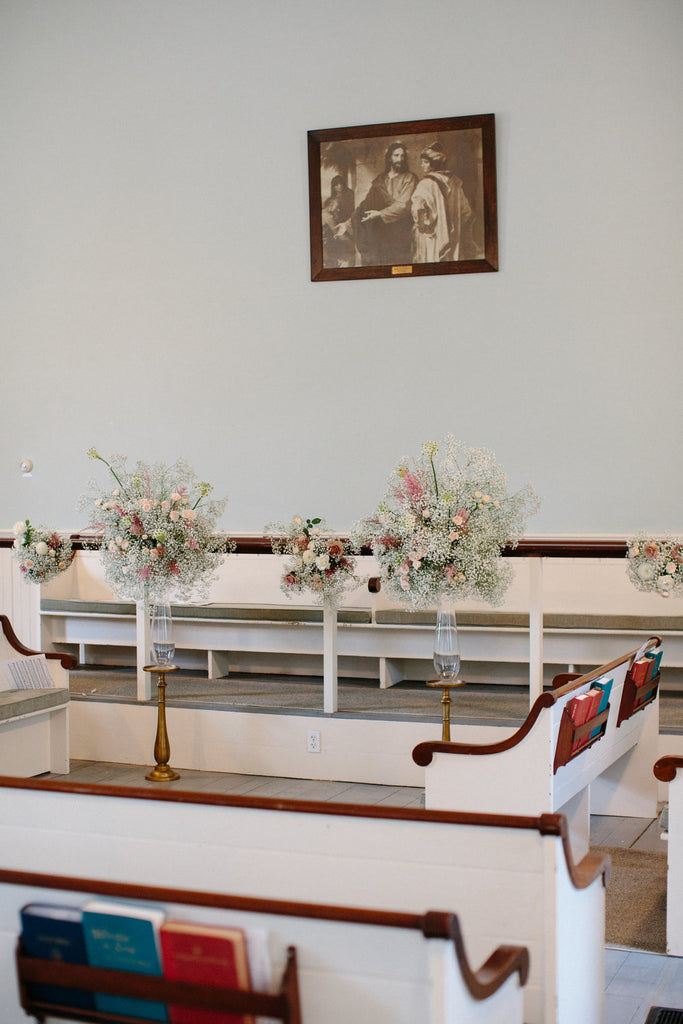 Interior photo of the church. Bouquets of roses and babies breath decorate the church.