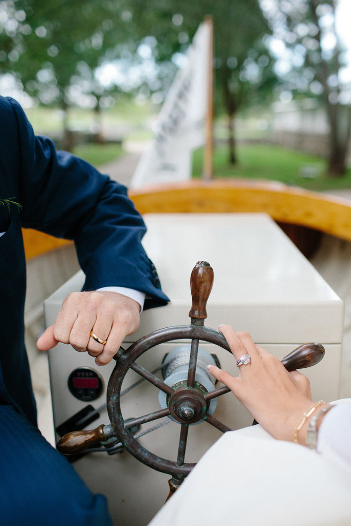 portrait of the newly weds rings on the steering wheel of the vintage boat.