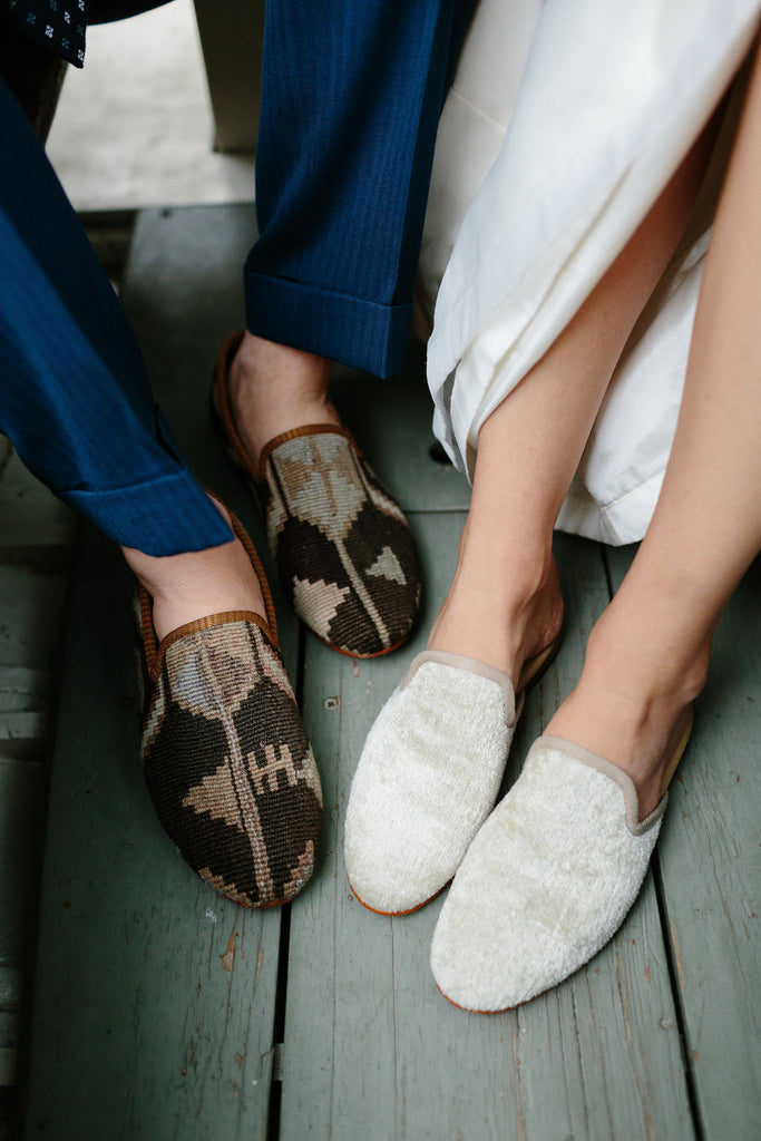 portrait of the grooms shoes, mens kilim loafers, and the brides shoes, pearl velvet slippers.