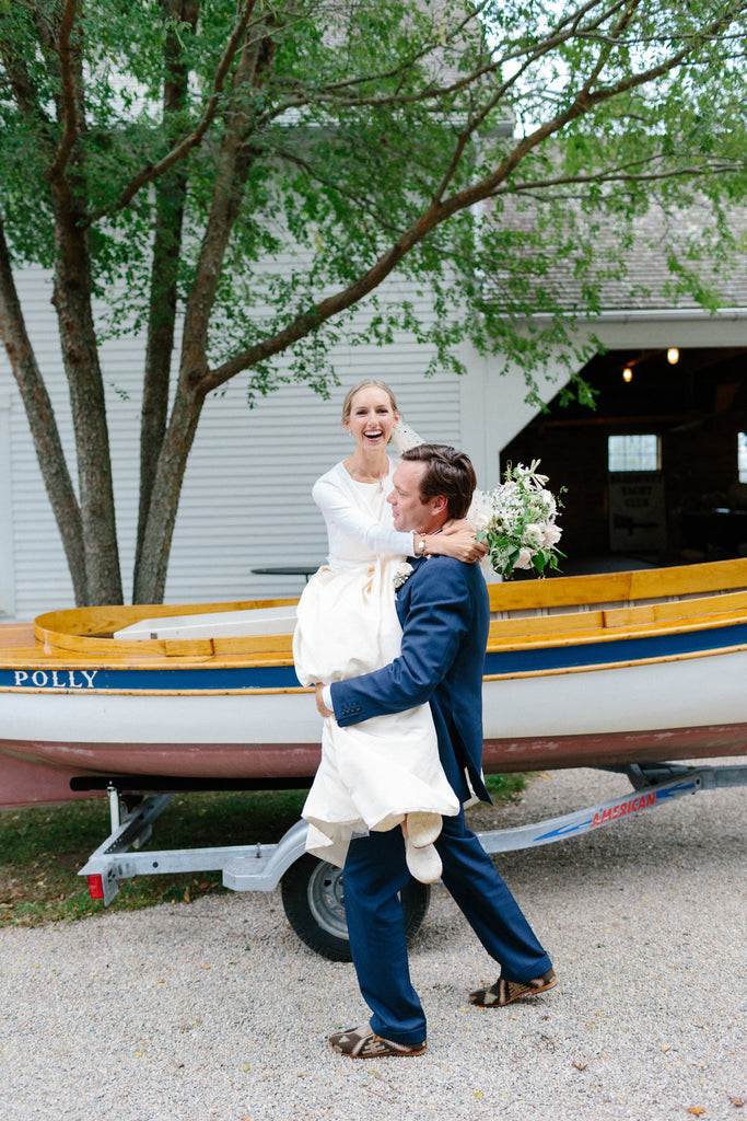groom carrying the bride out of the vintage boat they arrived in.