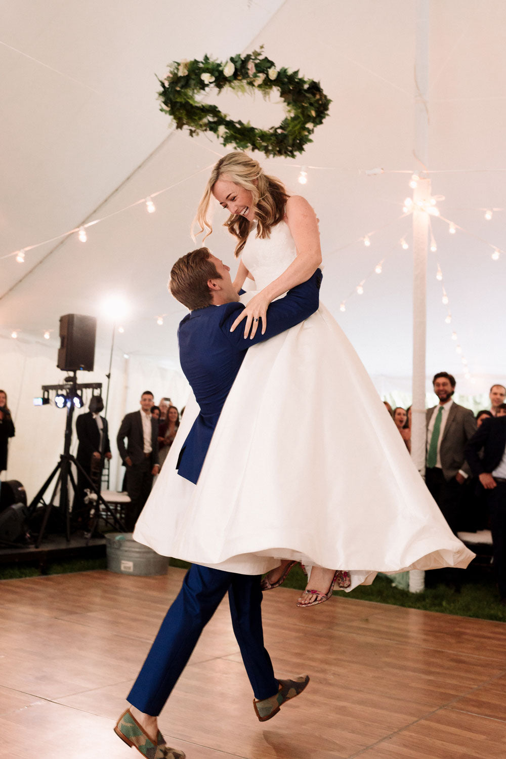 Alex Pardying wearing kilim shoes is lifting up Christina, his new wife, on dance floor at their wedding.