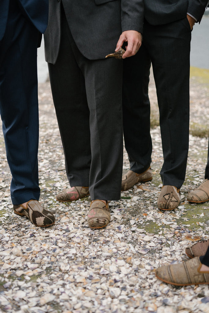 Groomsmen in the their custom kilim loafers standing on the beach.
