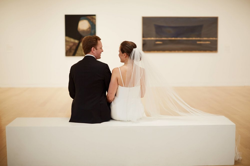 Bride and Groom siting looking at art