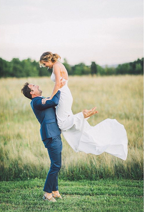 Nick holding up his bride in a field while wearing mens kilim loafers