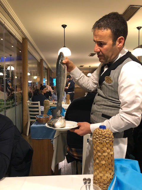 Waiter in Istanbul holding fish for dinner.