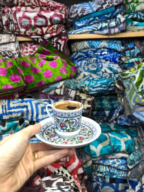 Teacup held in front of assorted colors of velvets in Istanbul.