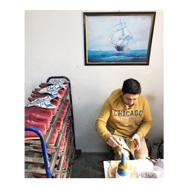 Cobbler in yellow working on kilim shoes and velvet slippers. He is seated in front of a white wall with a painting of a ship on it.