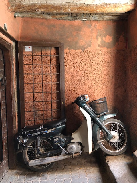 Motorcycle resting in salmon colored entryway.