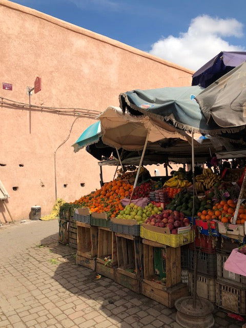 Colorful fruit market covered by umbrellas in Marrakech.