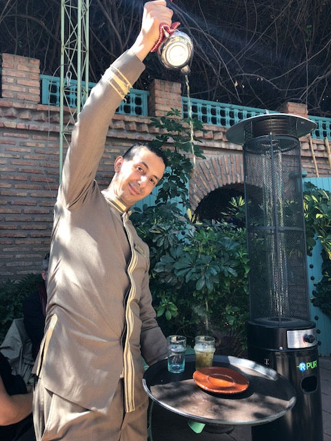 Having fun with waiter in Marrakech restaurant while he pours tea from pot above his head.