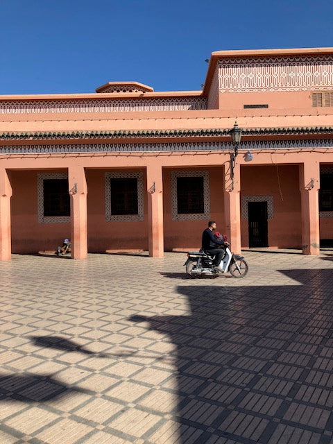 Man on motorcyle on tiled floor in front of salmon colored building.