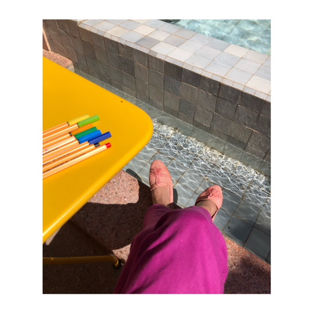 Sitting poolside in pink raffia loafers and pink pants, next to yellow table with colored drawing pens.