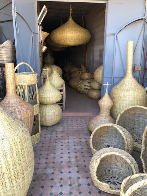 Assorted raffia items lining doorway into store.