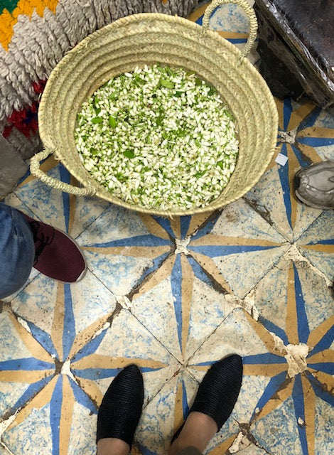 Black raffia slides on blue and yellow tiled floor in front of raffia bag filled with green and white seeds.