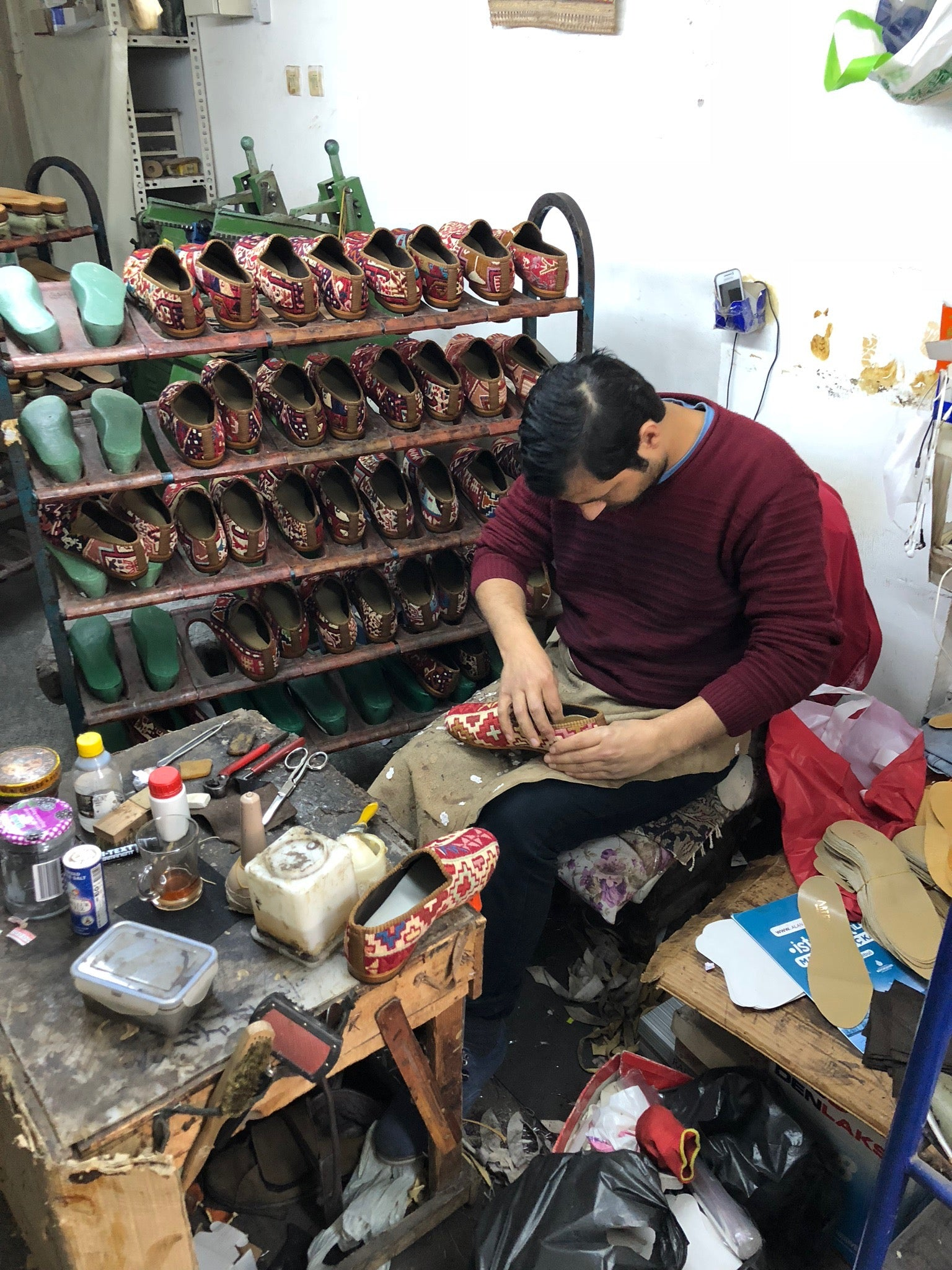 cobbler in workshop with kilim shoes