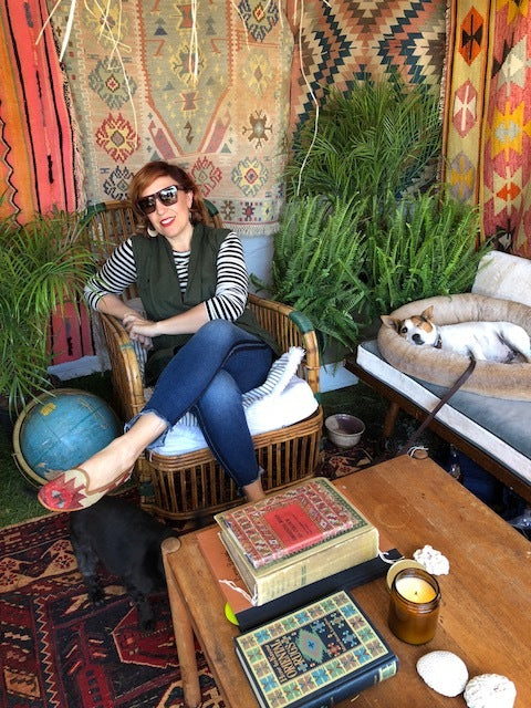 brimfield antique market customer in womens velvet slides and womens kilim loafers surrounded by kilim carpets and mens kilim loafers.