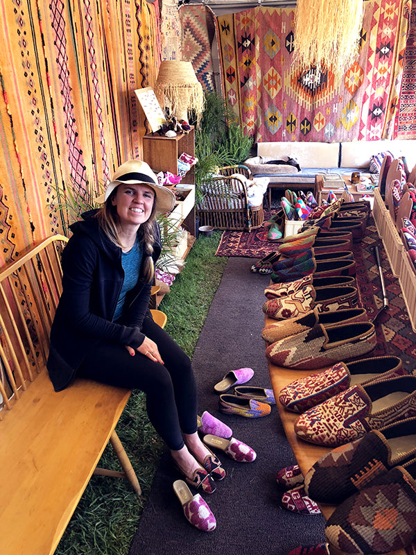 a customer at brimfield antique market choosing between woemsn kilim loafers and womens velvet slides. she is surrounded by kilim carpets and womens and mens kilim loafers.