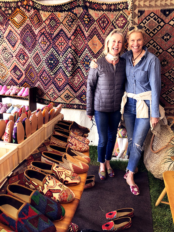 customer at brimfield antique market with womens kilim shoes surrounded by kilim carpets and mens kilim loafers.