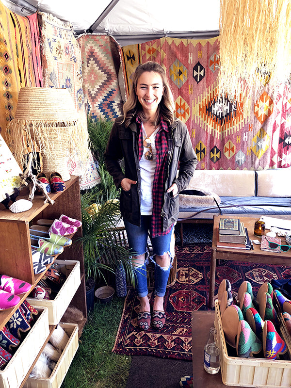 brimfield antique market customer in womens kilim slides and womens kilim loafers surrounded by kilim carpets and mens kilim loafers.