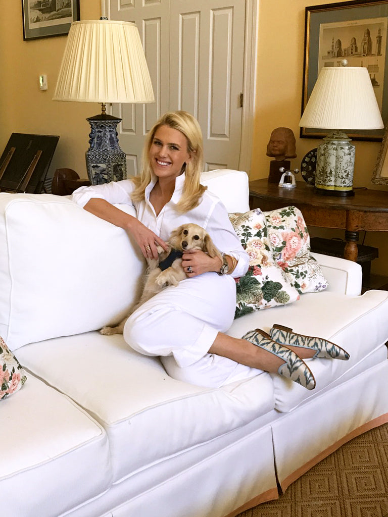 Julia, the owner and founder of India Amory, with dog on white couch in white and blue womens silk loafers.