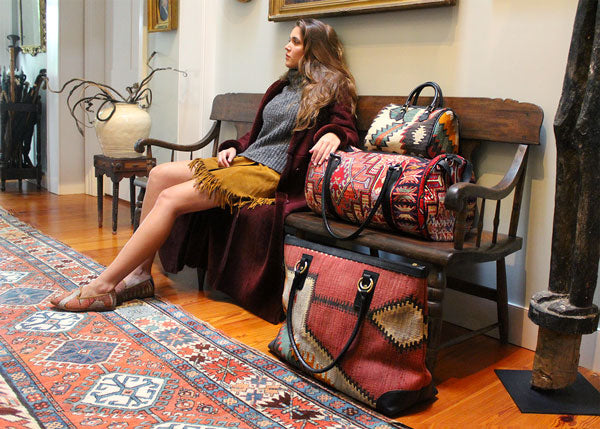 Model Yasmine sitting next to our kilim weekender, kilim bag, kilim baby duffle, and Kilim travel duffle.
