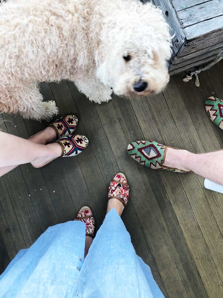 mens kilim smoking shoes, womens kilim sandals, and womens kilim slides on hardwood floor next to fluffy white puppy.
