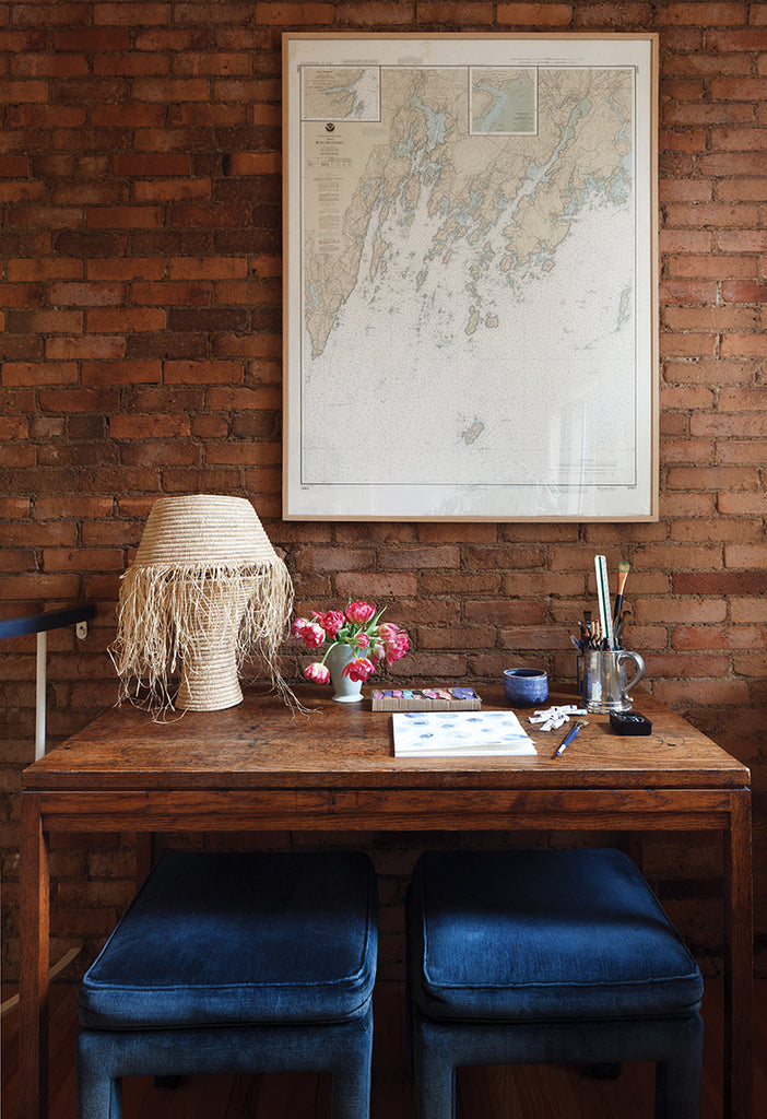 milicents brown working desk, covered with raffia lamp, paper, drawing utensils, and flowers. blue velvet chairs below.