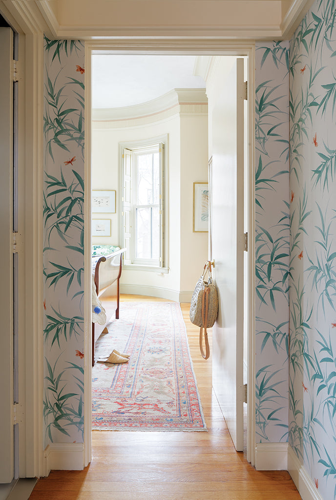 milicents hallway with leafy wallpaper, raffia marché bag. View into milicents room with raffia babouche shoes on a red kilim carpet.