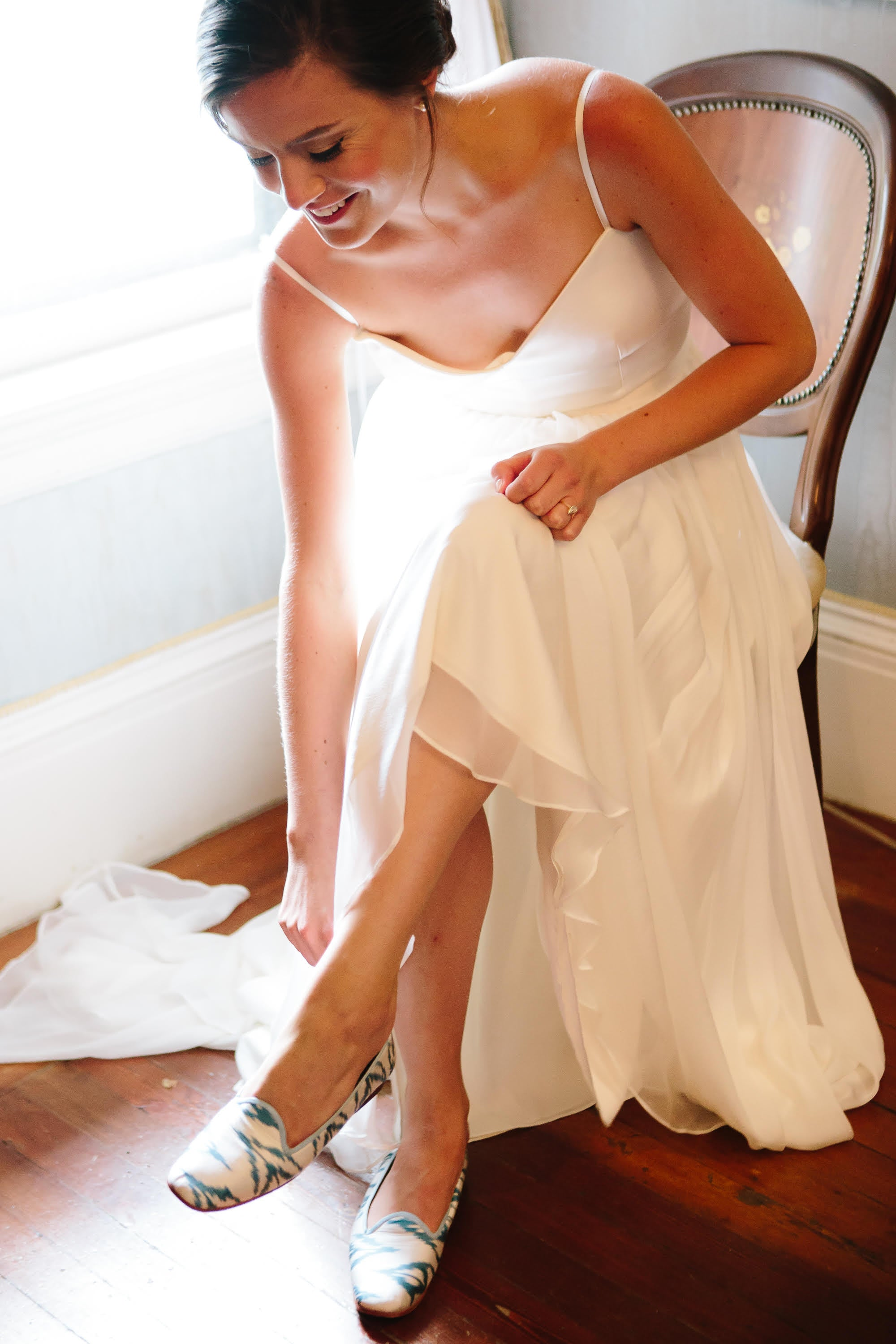 Riley Sheehey putting on our silk loafers in her wedding dress