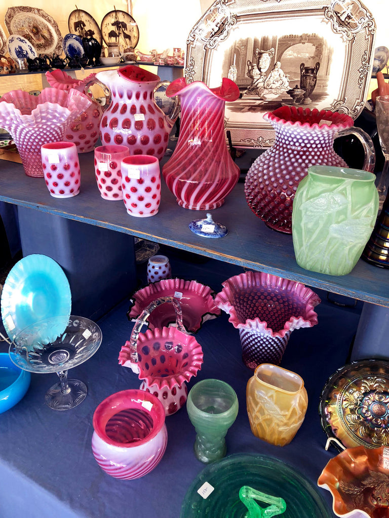 colorful assortment of vases and glass objects found at brimfield antique market.