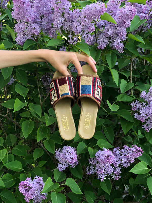 womens kilim sandals in sumak style being held in front of green plant with purple flowers.