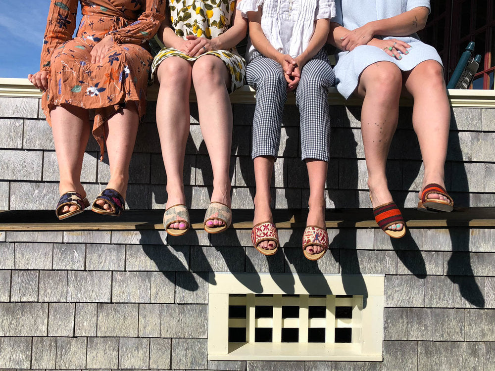 various kilim sandals on women sitting on roof of shingled house.