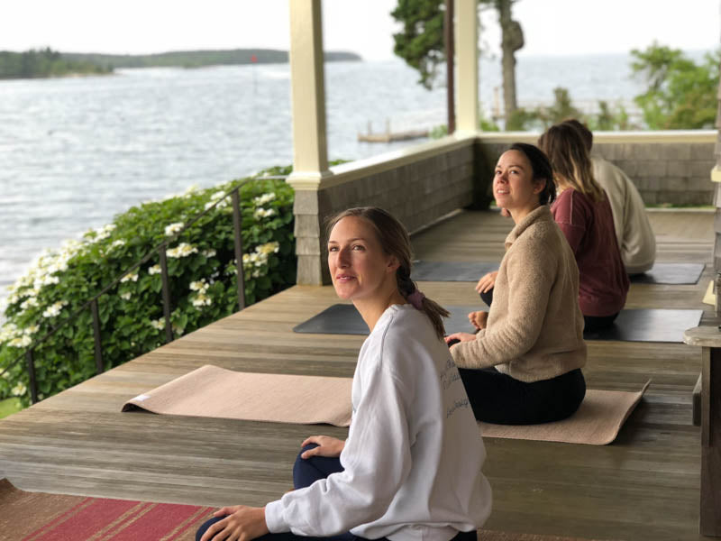 Milicent, McNeill and Carson sitting waterside preparing for yoga.