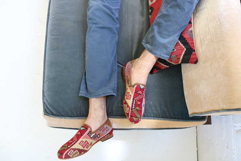 Mens kilim smoking shoes in sumak style on cousin with feet hanging off tan couch.