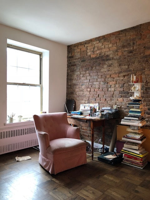 pauline's workspace at her studio, with pink velvet chair and desk.