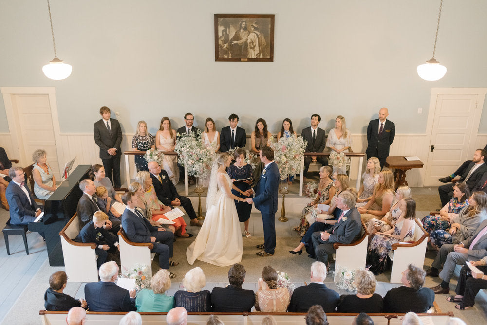 Bride and groom exchanging their vows surrounded by flower arrangements in the church