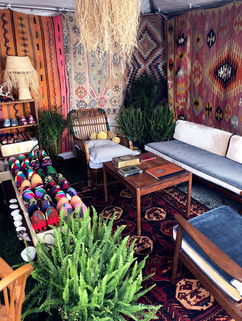 assortment of kilim smoking shoes, kilim loafers and velvet loafers displayed at Brimfield Antique Show on kilim carpet.