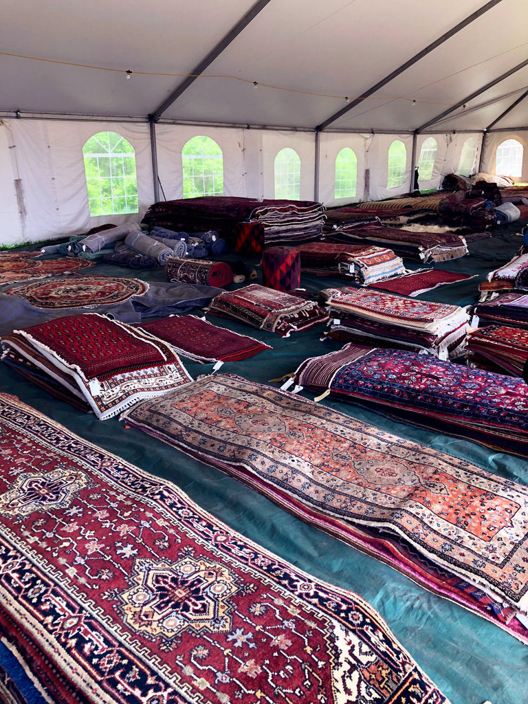 assortment of kilim carpets at brimfield antique market.