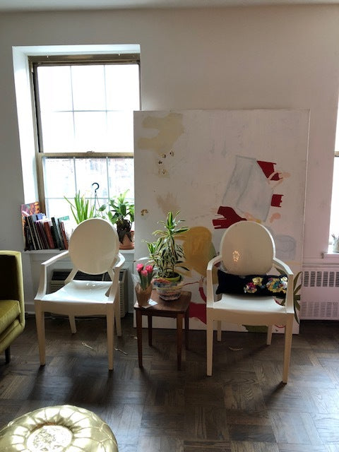 paulines studio with two white chairs, a small brown table between them with a plant and cactus on it. a painting behind the chairs and white walls.