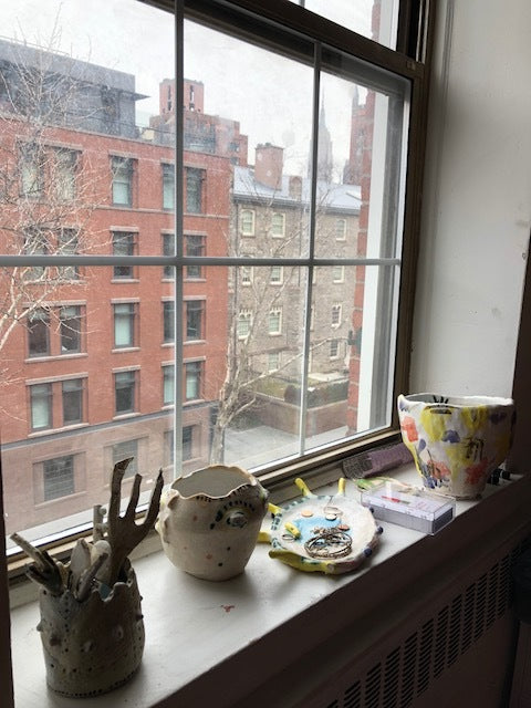 view from paulines apartment window with vases and sculptures lining the ledge of the window.