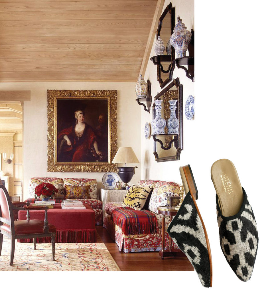 black and white velvet slippers for ibu movement paired with living room scene. living room has red themed assorted couches, painting, and kilim carpet.